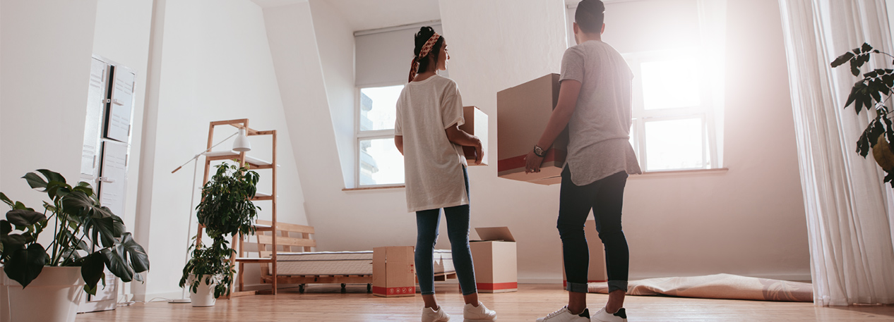 Man and woman in bedroom holding moving boxes