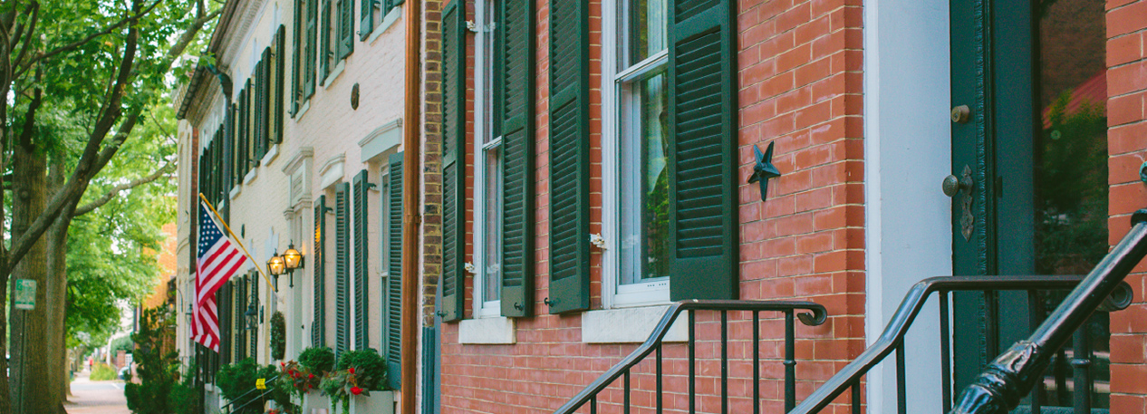 Row of brick townhouses with green shutters, one of which is displaying an American flag
