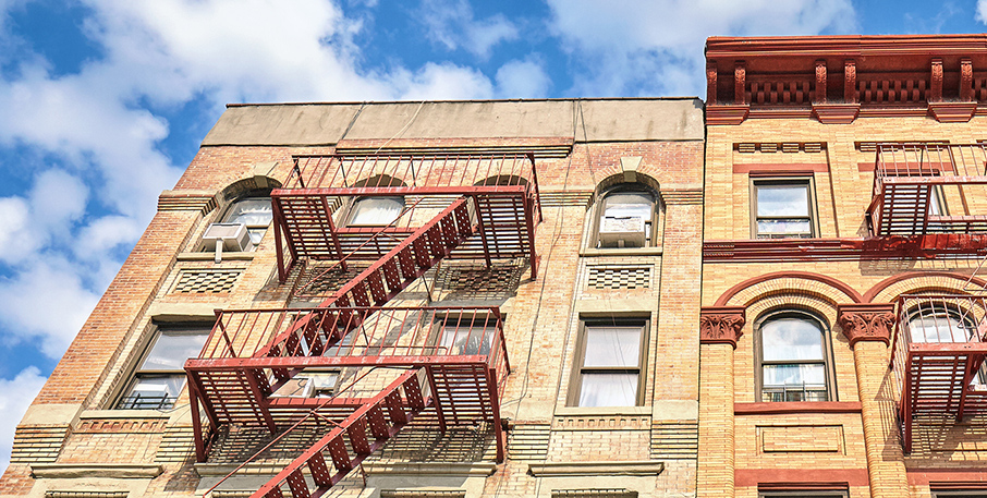 Top two floors of an urban apartment building with metal fire escapes