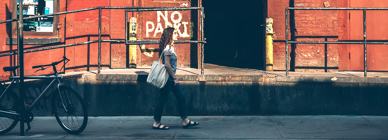 Woman walking down the street with tote bag, passing in front of a warehouse loading dock