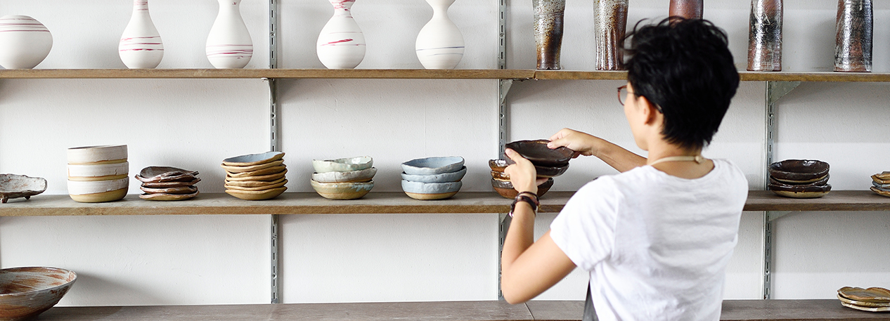 Woman placing vases and bowls on a display shelf in a pottery store