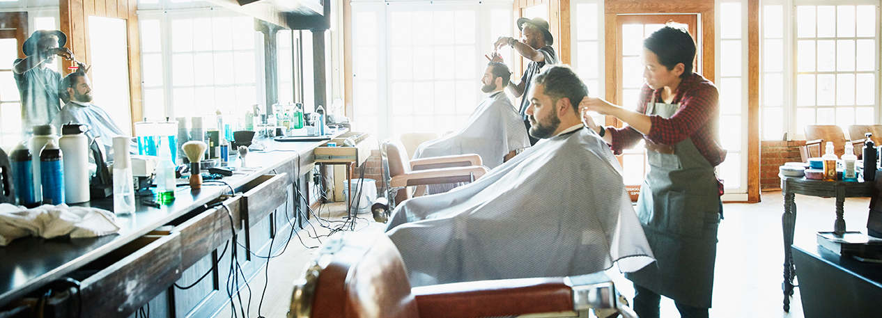 Men sitting in a barber chairs, getting their hair cut