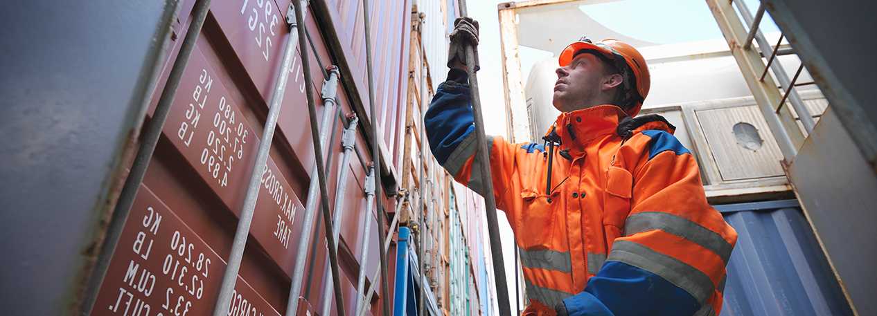 Worker in hardhat standing next to shipping container