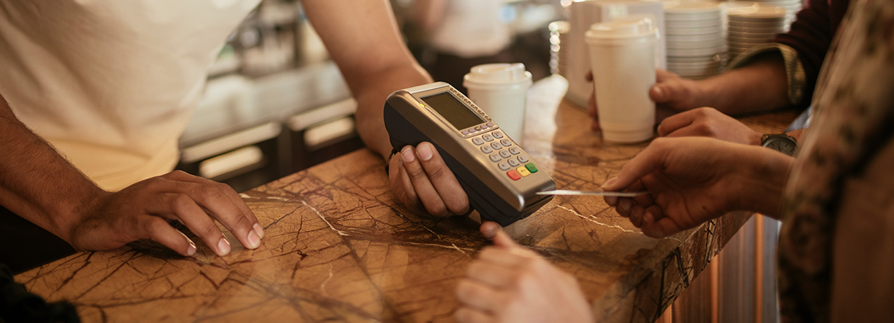 Close-up of person paying at a credit card reader in coffee shop