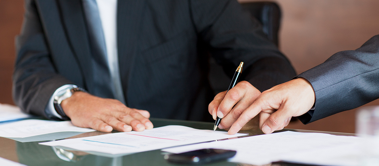 Man in suit signing a document at conference table