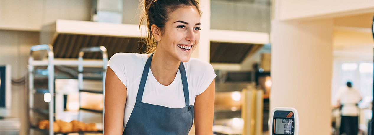 Woman in apron at counter in a restaurant