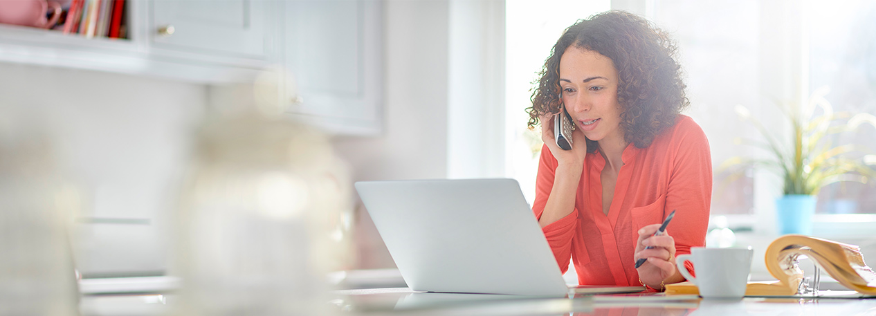 Woman speaking on telephone and looking at laptop computer