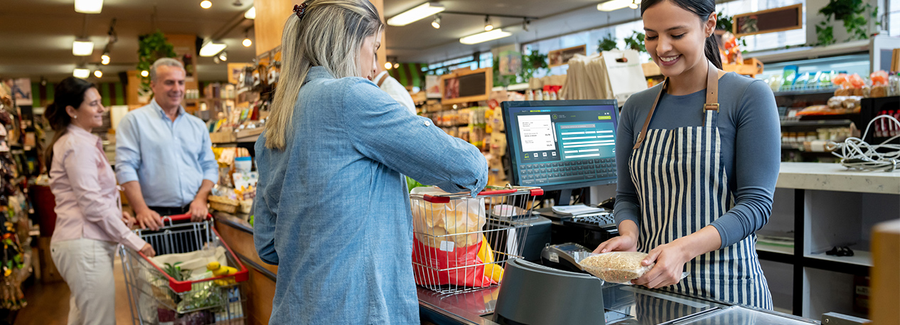 Cashier using the scanner at a grocery checkout