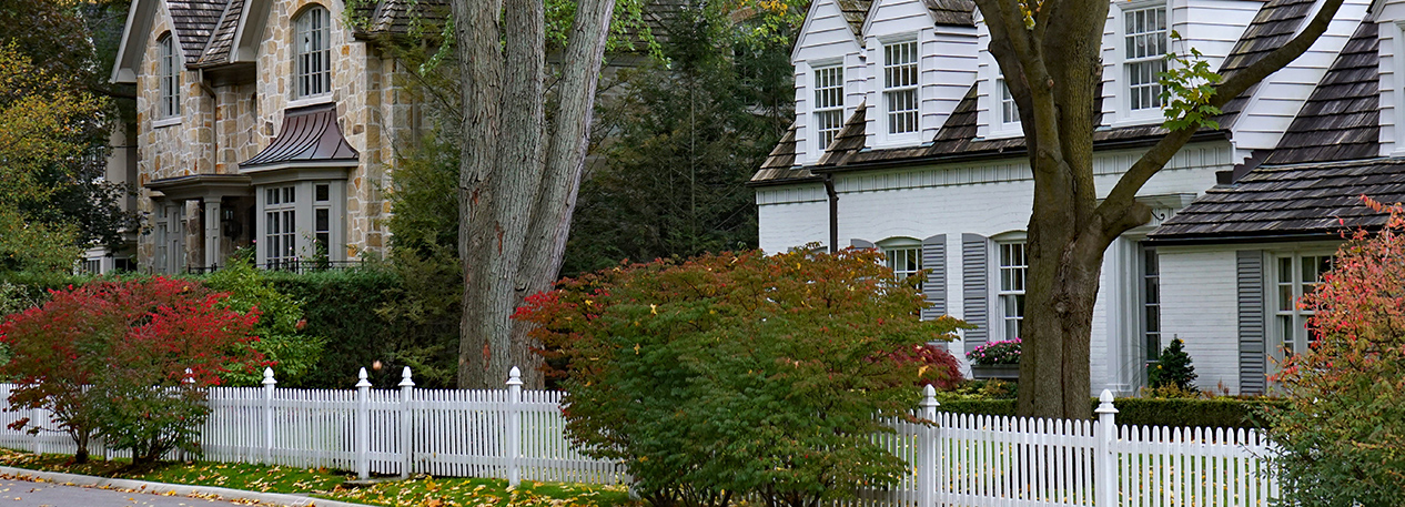 Upscale houses behind a picket fence on a tree-lined street