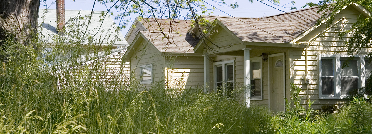 Home with overgrown lawn
