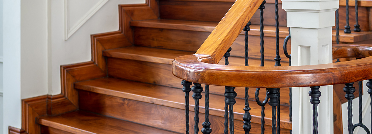 A flight of hardwood stairs and a wrought iron bannister with wooden handrail