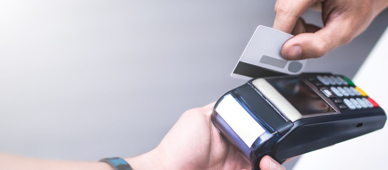 Close-up of a customer swiping a credit card through a hand-held reader