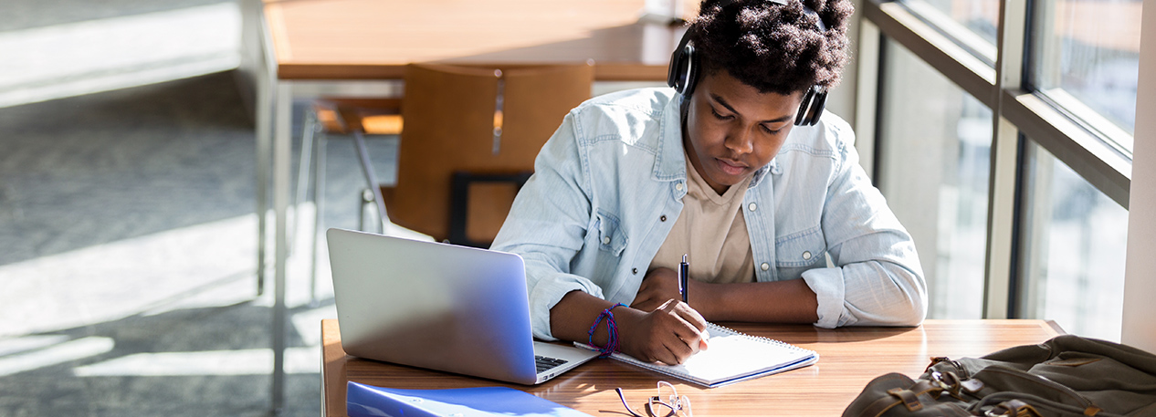 Student with headphones sitting at a small table with a laptop computer, writing in a notebook