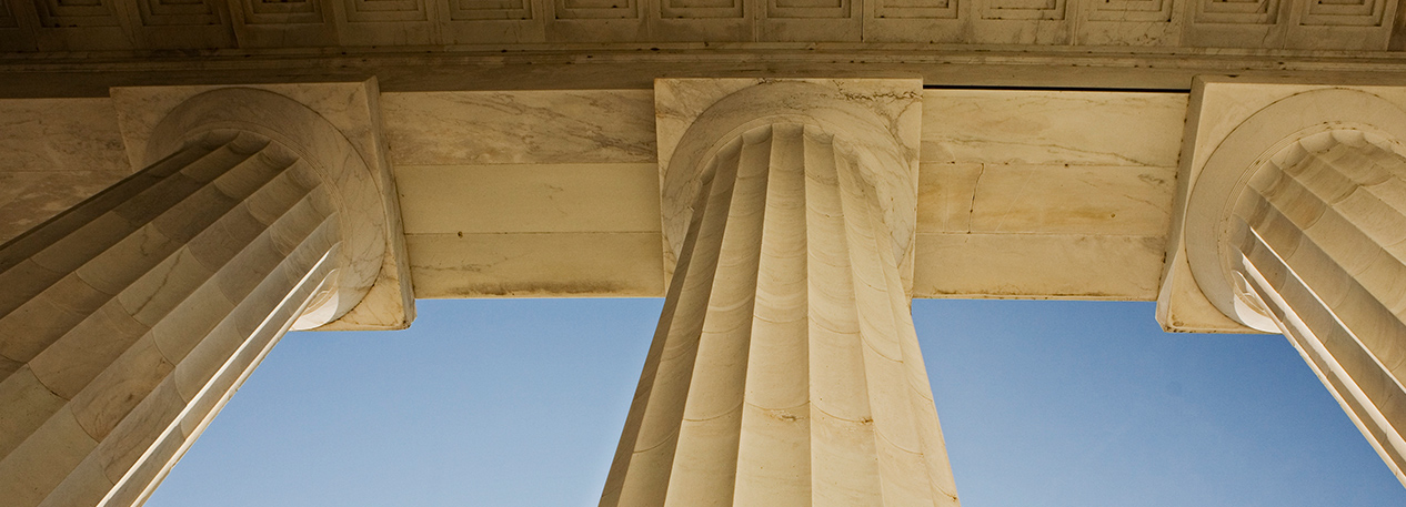 Looking up at the capitals of a row of fluted columns