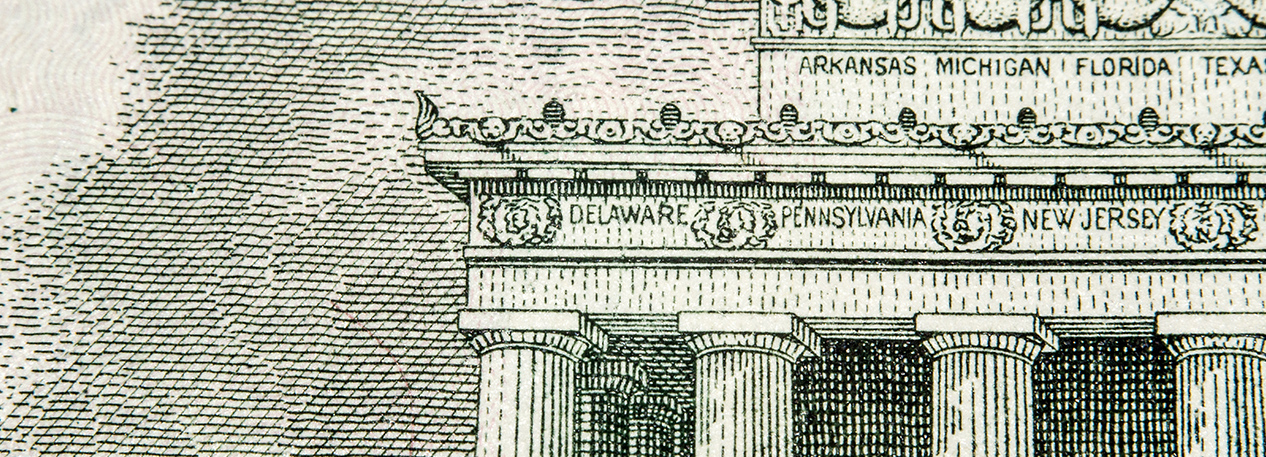 "Close-up of the Lincoln Memorial on the five-dollar bill with the inscriptions for ""Delaware,"" ""Pennsylvania,"" and ""New Jersey"" visible"