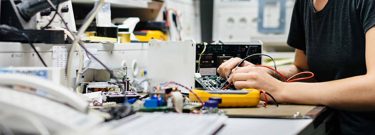 Female engineer working with electronic equipment at a workbench