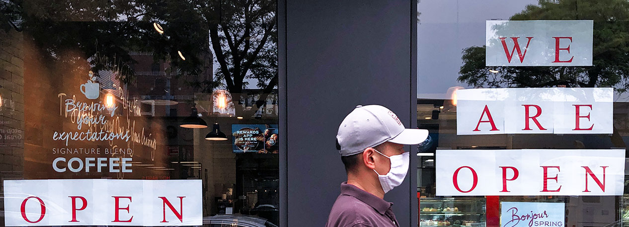 "A man in a face mask walks past a café with an ""open"" sign in the window"
