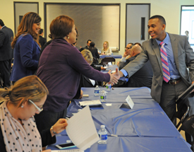 A graduate of the BankWork$ program in Los Angeles meets a bank recruiter at a job fair after a graduation ceremony.